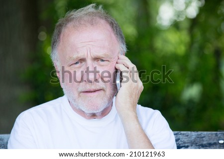 Closeup portrait, senior mature man in white t-shirt sitting on bench, having serious conversation on cell phone, isolated outside outdoors background - stock photo