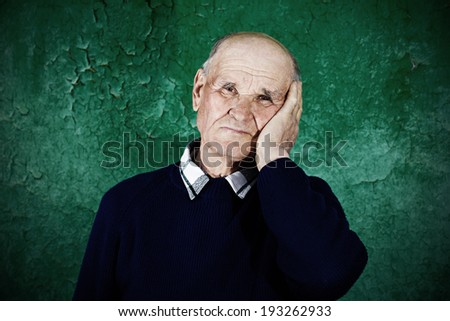 Closeup portrait, senior, sad old man thinking, daydreaming, looking away, palm, hand on face, isolated dark green background. Human emotions, facial expressions, feelings, life perception, reaction - stock photo