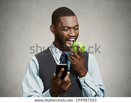 Closeup portrait serious business man, deal maker reading bad news on smart, mobile phone holding, eating green apple isolated black grey background. Human face expression, corporate executive emotion - stock photo