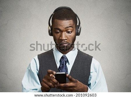 Closeup portrait serious looking, surprised businessman with headphones reading news, sms on smart phone, holding mobile isolated grey background. Human face expression, emotion, corporate executives - stock photo