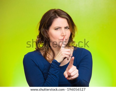Closeup portrait, serious mature woman placing finger, hand on lips, shhh gesture, be quiet, silence, isolated green background. Negative facial expression, sign, emotion, feelings, body language - stock photo