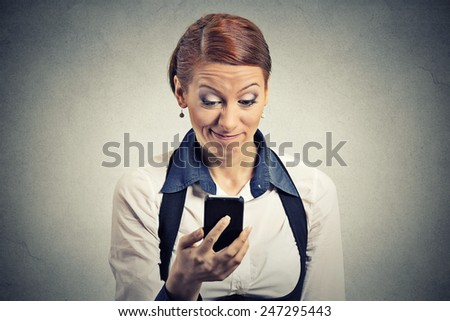 Closeup portrait serious worried displeased young businesswoman reading bad news on smart phone holding using mobile isolated grey wall office background. Negative human face expression emotion - stock photo
