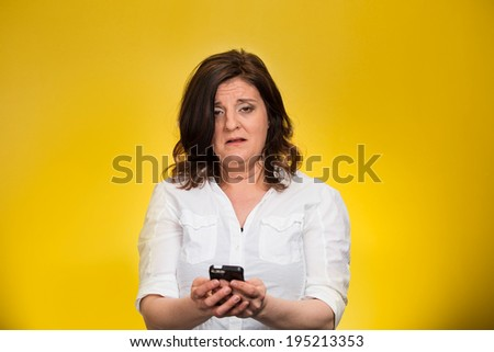Closeup portrait, shocked, business woman, corporate employee looking at cell phone, seeing bad text message, email, news isolated yellow background. Negative human emotion facial expression reaction - stock photo