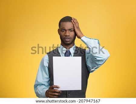 Closeup portrait shocked, funny looking young man, disgusted at monthly statement paper, test, application result isolated yellow background. Negative human emotion facial expression feeling. Bad news - stock photo