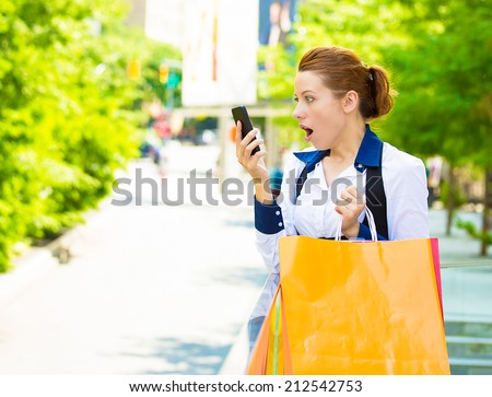 Closeup portrait shocked shopper woman looking at her smart phone, discovered great online deal, sale, receiving surprising news isolated outside new york city background. Emotions, facial expression - stock photo