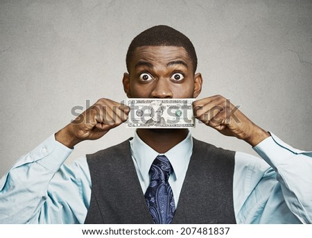 Closeup portrait shocked, surprised young corporate man in blue shirt holding twenty dollar bill to mouth, isolated grey background. Bribery concept in politics, business, diplomacy. Life perception - stock photo