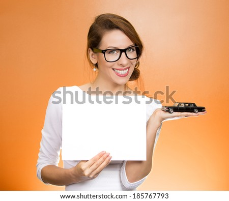 Closeup portrait smiling business woman in dress black glasses holding small car model, blank white paper in hands offering sign loan lease agreement isolated orange background. Bank financing credit. - stock photo