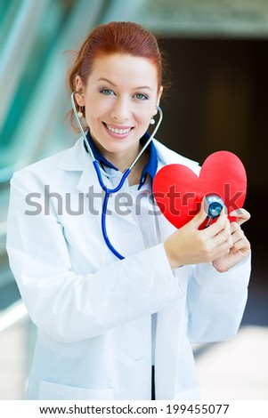 Closeup portrait smiling cheerful health care professional, pharmacist, dentist, nurse cardiologist doctor with stethoscope, holding listening heart isolated background hospital hallway. Patient visit - stock photo
