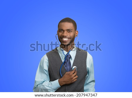 Closeup portrait smiling executive man, business person, worker listening to his heart with stethoscope isolated blue background. Preventive medicine, financial condition concept. Face expressions - stock photo