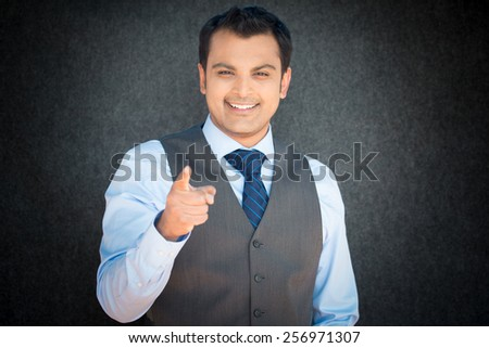 Closeup portrait, smiling handsome, excited, happy man pointing at you camera gesture with finger, isolated gray black background. Positive human emotion facial expression feeling signs symbols - stock photo