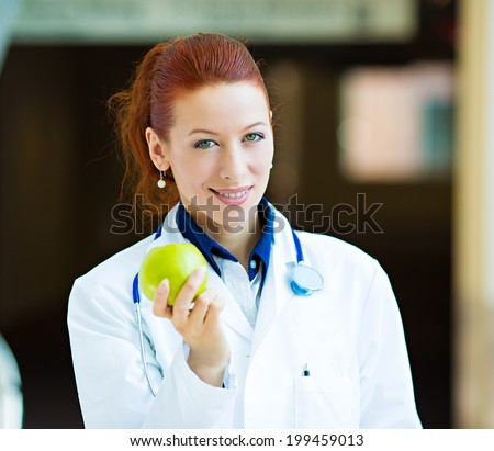 Closeup portrait smiling happy health care professional, doctor, nurse in lab coat offering green apple, isolated background hospital hallway. A day keeps doctor away concept. Nutrition, healthy diet - stock photo