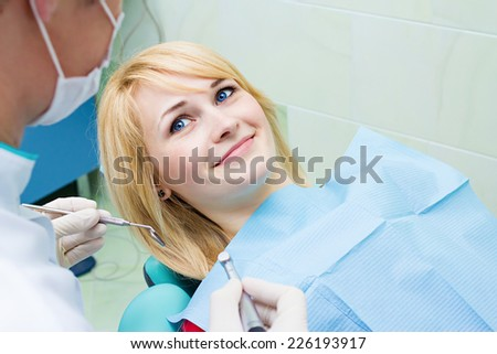 Closeup portrait smiling happy patient in dentist office, doctor holding angled mirror ready to examine teeth oral cavity. Clinic visit, preventive medicine annual check up. Positive facial expression - stock photo