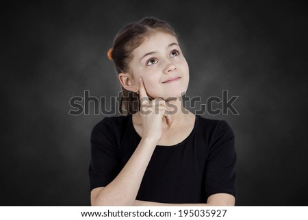 Closeup portrait, smiling, happy pensive little girl touching her cheek, thinking, daydreaming about something, looking up isolated black background. Human face expressions, emotion, reaction feelings - stock photo