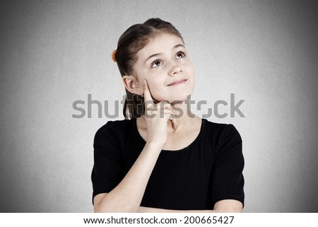 Closeup portrait, smiling, happy pensive little girl touching her cheek, thinking, daydreaming about something looking up isolated black background. Human face expressions, emotions, reaction feelings - stock photo