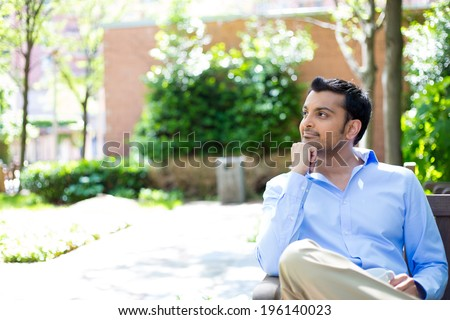 Closeup portrait, smiling, joyful, happy young business man, sitting, daydreaming nice things, isolated sunny outdoors, trees background. Positive human emotions facial expressions feelings - stock photo