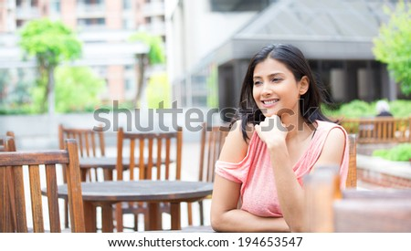 Closeup portrait, smiling, joyful, happy young woman, sitting, daydreaming nice things, isolated sunny outdoors, building background. Positive human emotions facial expressions feelings - stock photo