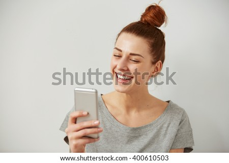Closeup portrait smiling or laughing young freelancer woman looking at phone seeing good news or photos with nice emotion on her face isolated wall background. Human emotion, reaction, expression. - stock photo