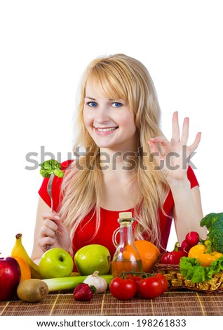 Closeup portrait smiling young woman, girl holding green broccoli on fork siting at table full of fruit vegetables giving ok sign making healthy diet choice isolated white background. Positive emotion - stock photo