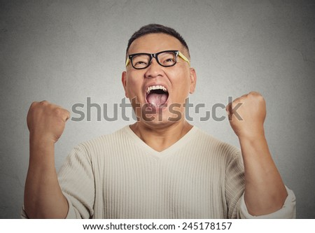 Closeup portrait successful student with glasses man winning, fists pumped celebrating success isolated grey wall background. Positive human emotion face expression. Life perception achievement vision - stock photo