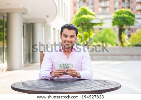 Closeup portrait, super happy excited successful young business man holding money dollar bills in hand, isolated background of trees, building. Financial reward - stock photo