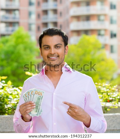 Closeup portrait, super happy excited successful young business man pointing to money dollar bills in hand, isolated background of trees, building. Financial reward - stock photo