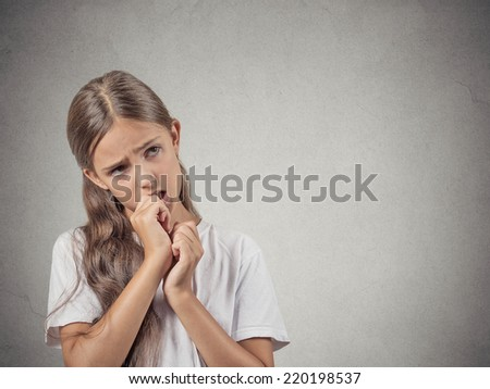 Closeup portrait teenager girl with finger in mouth, sucking thumb, biting fingernail in stress, clueless, isolated grey wall background. Negative emotion facial expression feeling. Body language - stock photo