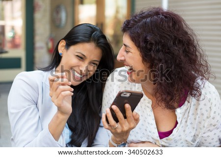 Closeup portrait two surprised girls looking at cell phone, discussing latest gossip news, sharing intimate moments, shopping, laughing at what they see, isolated outdoors background - stock photo
