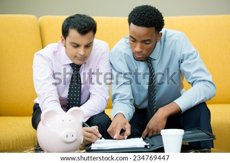 Closeup portrait, two young serious men in ties working on papers, signing documents, isolated yellow couch background with piggy bank and coffee on table foreground - stock photo