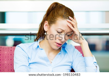 Closeup portrait unhappy business woman, head on hand sitting in armchair bothered by mistake having bad headache isolated background corporate office windows. Negative human emotion facial expression - stock photo