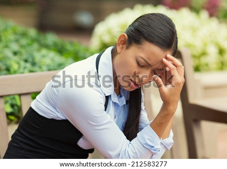 Closeup portrait unhappy business woman head on hand sitting on park bench bothered by mistake having bad headache isolated background outdoor office. Negative human emotion, facial expression feeling - stock photo