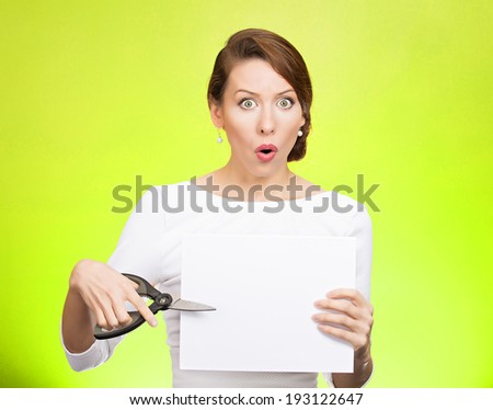 Closeup portrait, unhappy, confused, surprised, shocked business woman, funny looking female, worker employee cutting blank white paper, copy space, scissors isolated green background. Face expression - stock photo