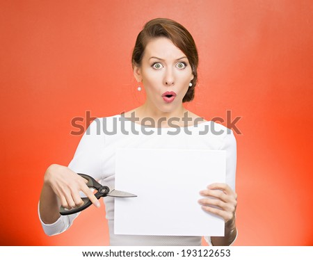 Closeup portrait, unhappy, confused, surprised, shocked business woman, funny looking female, worker employee cutting blank white paper, copy space, scissors isolated red background. Face expression - stock photo