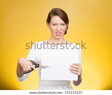 Closeup portrait, unhappy, skeptical, confused, displeased business woman, funny female, worker, employee cutting blank white paper, copy space, scissors isolated yellow background. Facial expressions - stock photo
