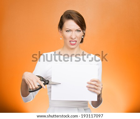 Closeup portrait, unhappy, skeptical, confused, displeased business woman, funny female, worker, employee cutting blank white paper, copy space, scissors isolated orange background. Facial expressions - stock photo