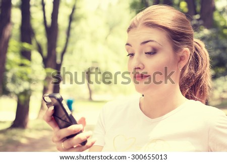Closeup portrait upset skeptical unhappy serious woman talking texting on phone displeased with conversation isolated park trees outdoors background. Negative human emotion face expression feeling - stock photo
