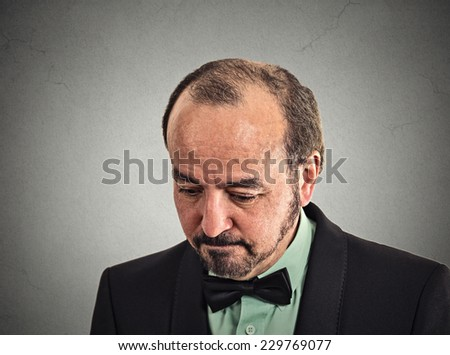 Closeup portrait very sad, depressed, desperate, alone, disappointed in life middle aged man looking down isolated on grey wall background with copy space. Negative human emotions, face expression - stock photo