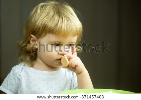 Closeup portrait view of one adorable cute small baby boy with blonde hair eating healthy food of porridge or coocked semolina and little pastry holding in hand indoor, horizontal picture - stock photo