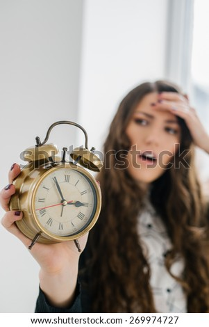 Closeup portrait woman extending hand to alarm clock. Human face expression, emotion, feeling.  - stock photo