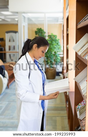 Closeup portrait, woman healthcare professional with stethoscope enjoying reading, studying in library room - stock photo