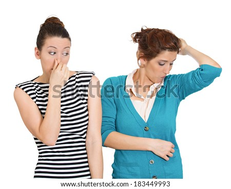 Closeup portrait, woman looking at female closing, covering nose, something stinks, very bad smell, odor. Girl sniffs herself. Isolated white background. Negative emotion, facial expression, feeling - stock photo