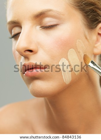 closeup portrait woman trying different shades foundation - stock photo
