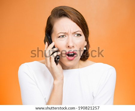 Closeup portrait young angry business woman, corporate employee talking on cell phone, having unpleasant, bad conversation, isolated orange background. Negative emotions, facial expressions, reaction - stock photo