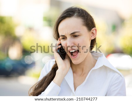Closeup portrait young angry business woman, corporate employee talking on cell phone, having unpleasant, bad conversation, isolated outdoor background. Negative emotions, facial expressions, reaction - stock photo