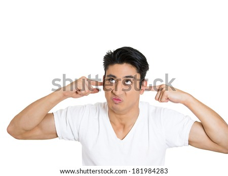Closeup portrait young, angry, unhappy, stressed man covering his ears, looking up, to say, stop making loud noise it's giving headache, isolated white background. Negative emotions, face expressions - stock photo