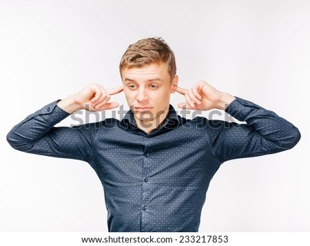 Closeup portrait young, angry, unhappy, stressed man covering his ears, looking up, to say, stop making loud noise it's giving headache. Negative emotions, face expressions - stock photo