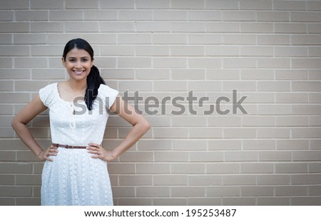 Closeup portrait, young beautiful business woman in white dress smiling, posing, hands on hips, isolated gray brick background vignette. Positive human emotion facial expression - stock photo