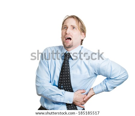 Closeup portrait young business man, corporate employee, looking miserable, holding lower back with hands, doubling over in kidney pain, isolated white background. Nephrolithiasis. face expression - stock photo