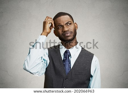 Closeup portrait young company business man thinking, daydreaming trying hard to remember something looking upward, isolated black background. Negative emotions, facial expressions, feelings, reaction - stock photo