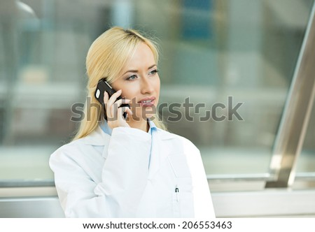 Closeup portrait, young confident, attractive female doctor, healthcare professional holding smartphone, talking on phone with patient isolated background hospital office.  Clinic visit health care - stock photo