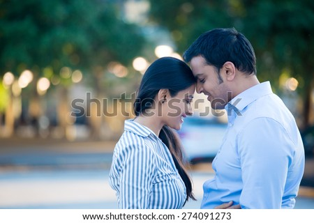 Closeup portrait, young couple in blue shirt, head to head, eyes closed in love smitten, isolated outdoors outside background. Happy moments, positive emotions - stock photo